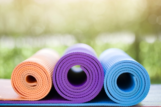 many yoga mats on the wood table in the garden